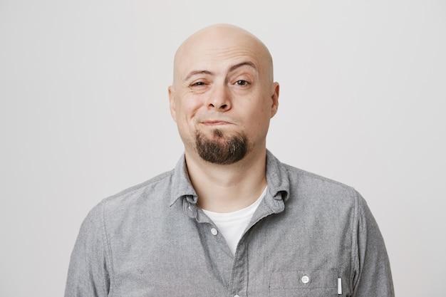Kale glimlachende man van middelbare leeftijd met baard op zoek