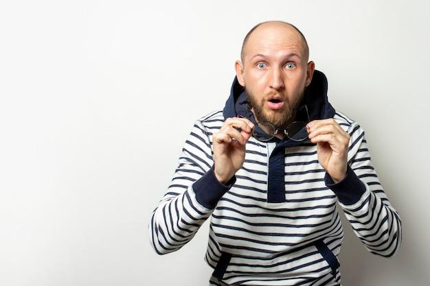 Kale jonge man met een baard, een trui met capuchon zette zijn bril af met een verbaasd gezicht op een geïsoleerd wit. een gebaar van verbazing, shock. kopieer ruimte