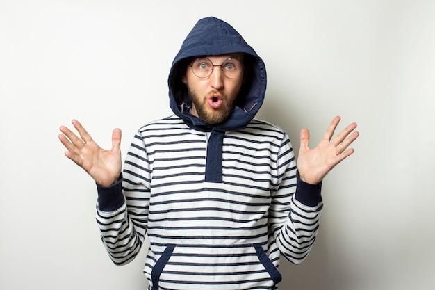 Kale jonge man met een baard in glazen, een trui met een capuchon en een verbaasd gezicht op een afgelegen wit. man in de kap