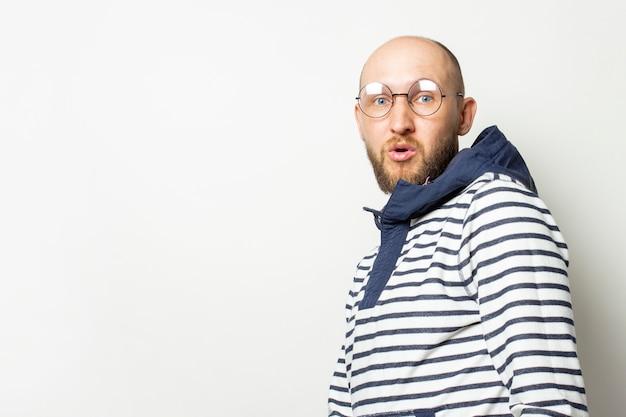 Kale jonge man met een baard in glazen, een trui met een capuchon, met een bang gezicht op een afgelegen wit. gebaar van angst, verrassing