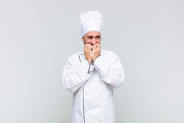 Kale man die bezorgd, angstig, gestrest en bang kijkt, vingernagels bijt en naar laterale kopieerruimte kijkt