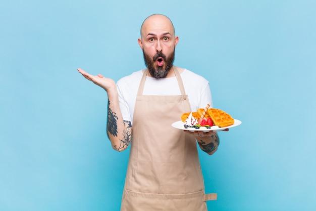 Kale man die verbaasd en geschokt kijkt, met open mond een voorwerp vasthoudend met een open hand opzij