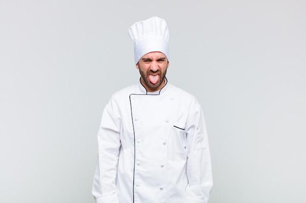 Kale man die walgt en geïrriteerd voelt, tong uitsteekt, niet van iets smerigs en vies houdt