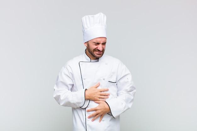 Kale man die zich angstig, ziek, ziek en ongelukkig voelt, pijnlijke buikpijn of griep heeft