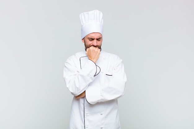 Kale man die zich ernstig, bedachtzaam en bezorgd voelt, zijwaarts staart met de hand tegen de kin gedrukt