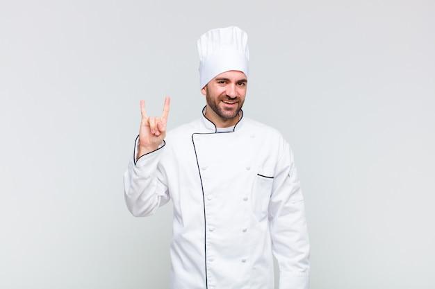 Kale man die zich gelukkig, leuk, zelfverzekerd, positief en rebels voelt en een rock of heavy metal-bord met de hand maakt