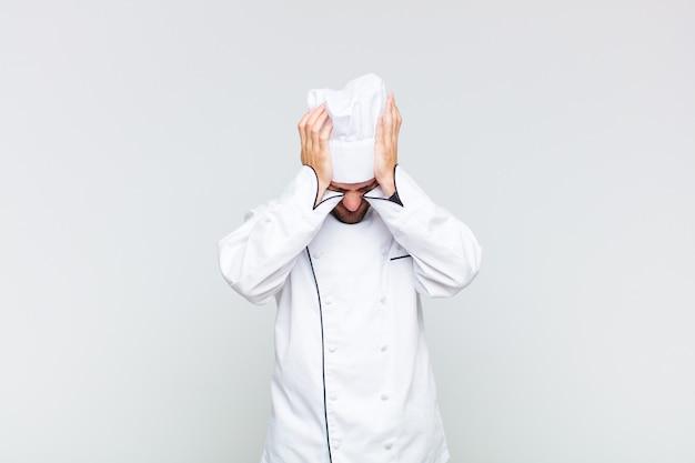 Kale man die zich gestrest en gefrustreerd voelt, zijn hand opheft naar het hoofd, zich moe, ongelukkig voelt en migraine heeft