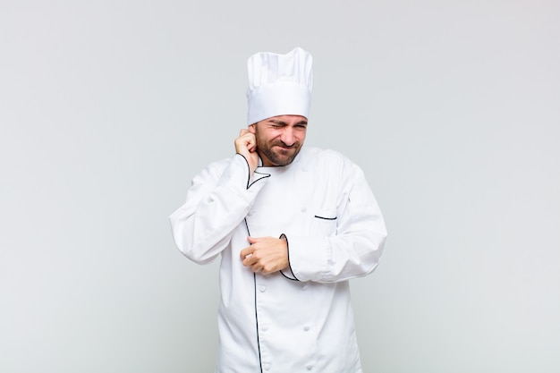 Kale man die zich gestrest, gefrustreerd en moe voelt, pijnlijke nek wrijft, met een bezorgde, onrustige blik