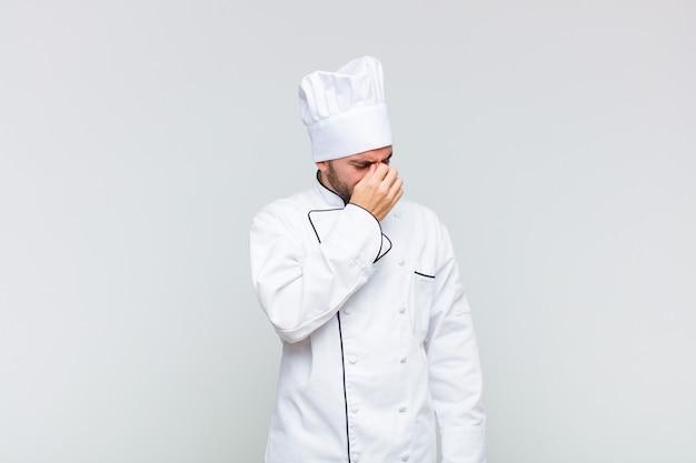 Kale man die zich gestrest, ongelukkig en gefrustreerd voelt, het voorhoofd aanraakt en lijdt aan migraine of ernstige hoofdpijn