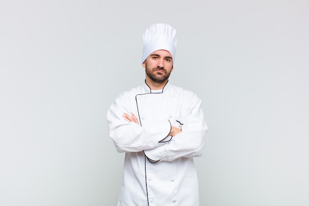 Kale man die zich ontevreden en teleurgesteld voelt, ernstig, geïrriteerd en boos kijkt met gekruiste armen