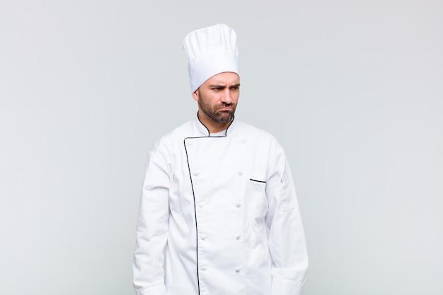 Kale man die zich verdrietig, boos of boos voelt en opzij kijkt met een negatieve houding, fronsend bij onenigheid