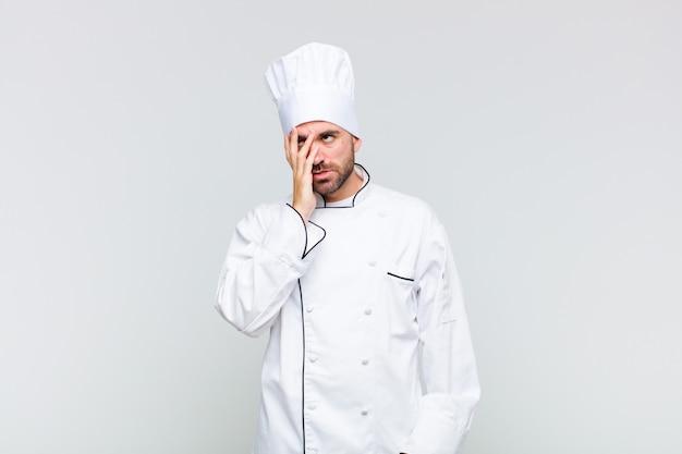 Kale man die zich verveeld, gefrustreerd en slaperig voelt na een vermoeiende, saaie en vervelende taak, gezicht met hand vasthoudend