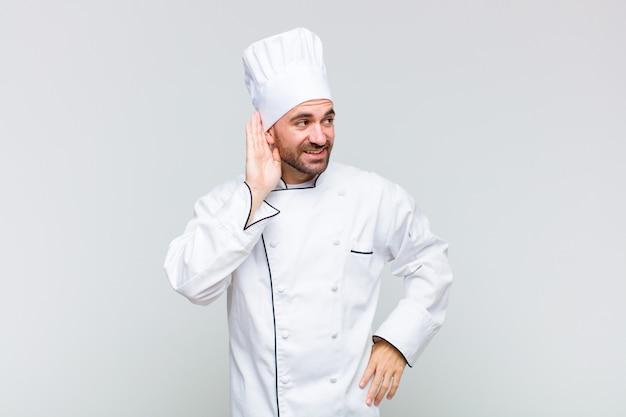 Kale man glimlachend, nieuwsgierig naar de zijkant kijkend, proberend naar roddels te luisteren of een geheim af te luisteren