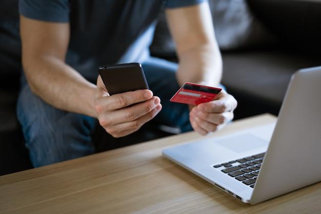 Kale man in een medisch masker met een creditcard zit op de bank op een laptop met een telefoon in zijn hand, het concept van online winkelen in een online winkel