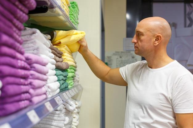 Kale man kiest handdoeken op de planken in een winkel, shopping concept