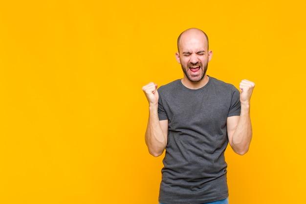 Kale man kijkt buitengewoon blij en verrast, viert succes, schreeuwt en springt