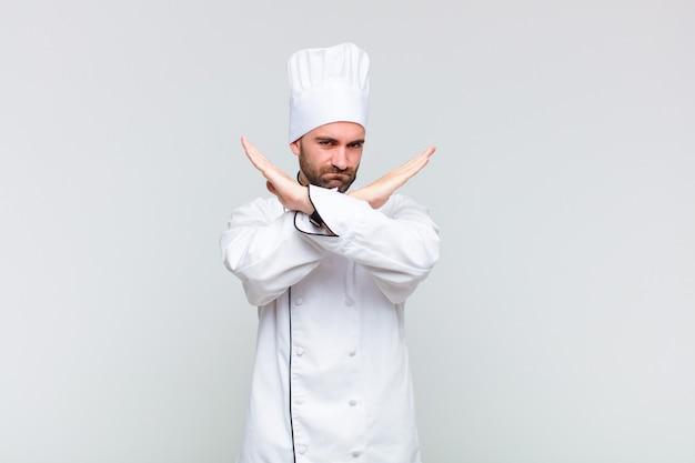 Kale man kijkt geïrriteerd en ziek van je houding, genoeg zeggend! handen voorover gekruist, zeggend dat je moet stoppen
