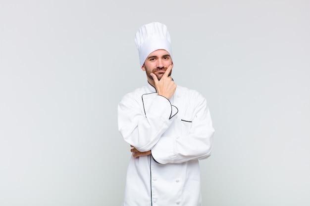 Kale man kijkt serieus, attent en wantrouwend, met één arm gekruist en hand op kin, opties voor het wegen