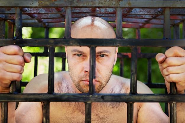 Kale man kijkt van achter de gevangeniscel, hij werd opgesloten als gevolg van ontvoering, arrestatie, rechterlijke beslissing over detentie of veroordeling.