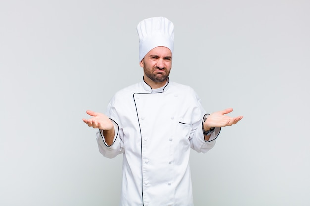 Kale man kijkt verbaasd, verward en gestrest, vraagt zich af tussen verschillende opties, voelt zich onzeker