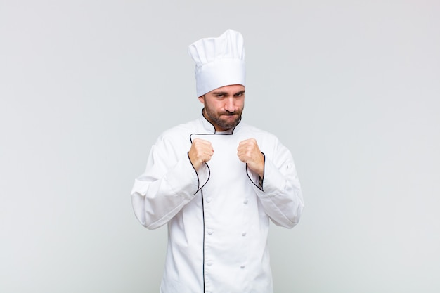 Kale man kijkt zelfverzekerd, boos, sterk en agressief, met vuisten klaar om te vechten in bokspositie