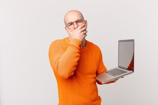 Kale man met computer die mond bedekt met handen met een geschokte, verbaasde uitdrukking, een geheim bewaren of oeps zeggen