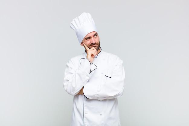 Kale man met een geconcentreerde blik, verwonderd met een twijfelachtige uitdrukking, opkijkend en opzij