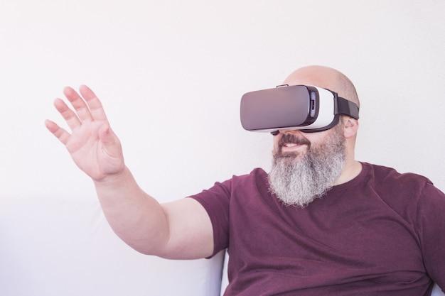 Kale man met een grote baard met een virtual reality-bril of een kastanjebruin t-shirt met een opgeheven hand op een witte muur