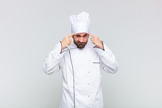Kale man met een serieuze en geconcentreerde blik, brainstormend en denkend over een uitdagend probleem