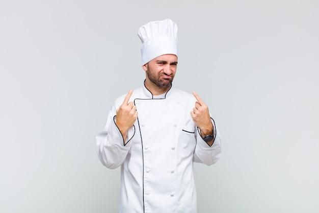 Kale man met een slechte houding die er trots en agressief uitziet, naar boven wijst of een grappig teken maakt met de handen