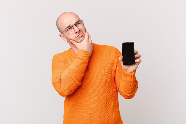 Kale man met een smartphone die denkt, zich twijfelachtig en verward voelt, met verschillende opties, zich afvragend welke beslissing hij moet nemen
