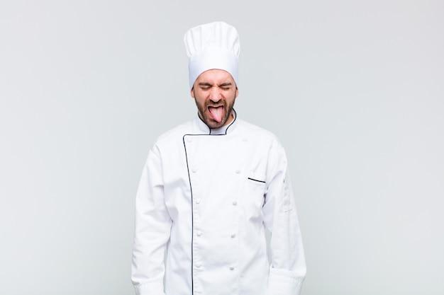 Kale man met vrolijke, zorgeloze, rebelse houding, grappen maken en tong uitsteken, lol maken