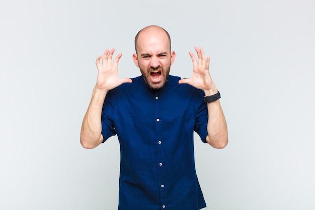 Kale man schreeuwen in paniek of woede, geschokt, doodsbang of woedend, met de handen naast het hoofd