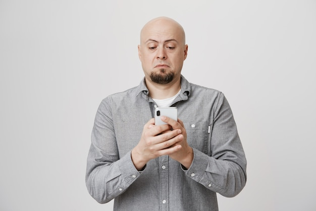 Kale man van middelbare leeftijd die telefoon zonder bril bekijkt