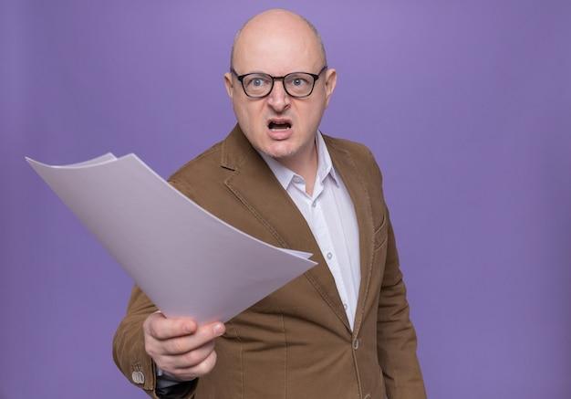 Kale man van middelbare leeftijd in pak die een bril draagt die blanco pagina's houdt die opzij kijken met agressieve uitdrukking die zich over purpere muur bevindt