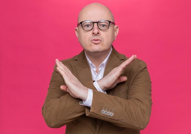 Kale man van middelbare leeftijd in pak die een bril draagt die naar de voorkant kijkt met een ernstig gezicht, stopgebaar maakt die de handen kruist die zich over roze muur bevinden