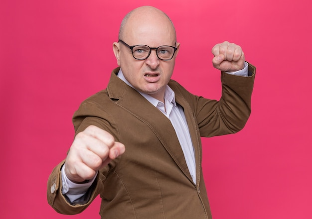 Kale man van middelbare leeftijd in pak die een bril draagt en naar de voorkant kijkt met een boos gezicht met gebalde vuisten gaat vechten staande over roze muur