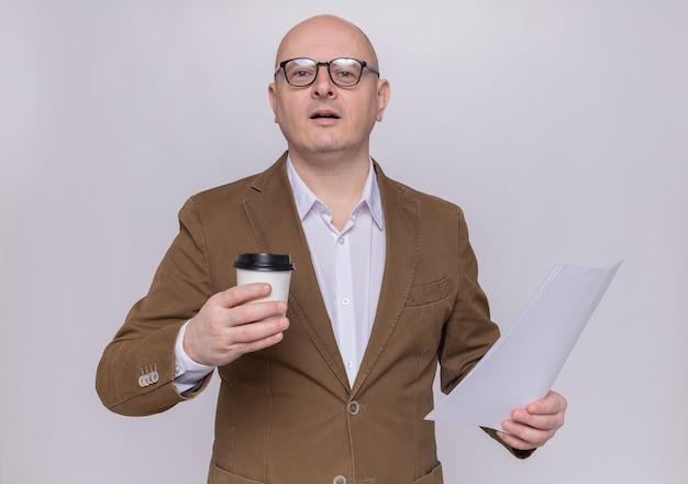 Kale man van middelbare leeftijd in pak die glazen draagt die peper-kop en lege pagina houden die voorzijde met ernstige zekere uitdrukking bekijken die zich over witte muur bevinden