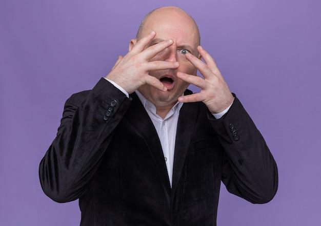Kale man van middelbare leeftijd in pak die zijn gezicht bedekt met handpalmen die naar voren kijken door vingers die scard zijn die zich over paarse muur bevinden