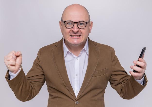 Kale man van middelbare leeftijd in pak met bril die mobiele telefoon met gebalde vuist vasthoudt met agressieve uitdrukking die wild wordt staande over witte muur