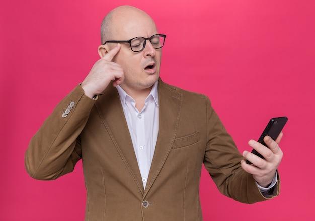 Kale man van middelbare leeftijd in pak met bril die naar zijn mobiele telefoon kijkt die verward en erg angstig over roze muur staat