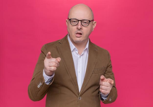 Kale man van middelbare leeftijd in pak met bril glimlachend zelfverzekerd wijzend met wijsvingers aan de voorkant staande over roze muur
