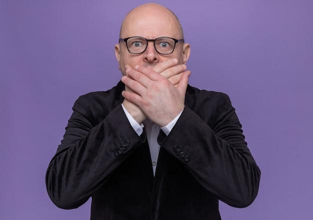 Kale man van middelbare leeftijd in pak met bril kijken naar voorkant bein geschokt bedekkend mond met handen die zich over paarse muur bevinden