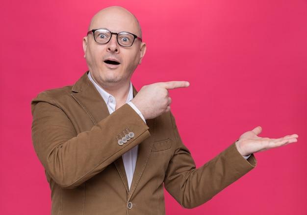 Kale man van middelbare leeftijd in pak met bril kijkend naar voorzijde verrast en blij wijzend met wijsvingers naar de zijkant staande over roze muur