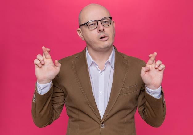 Kale man van middelbare leeftijd in pak met bril maken wens kruising vingers met hoop expressie staande over roze muur