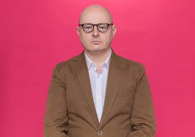 Kale man van middelbare leeftijd in pak met bril op zoek naar voorzijde met ernstige zelfverzekerde uitdrukking staande over roze muur
