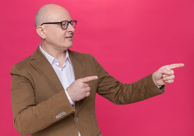 Kale man van middelbare leeftijd in pak met bril opzij glimlachend zelfverzekerd wijzend met wijsvingers naar de zijkant staande over roze muur