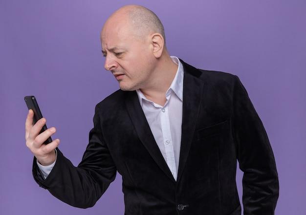 Kale man van middelbare leeftijd in pak met mobiele telefoon kijken geïntrigeerd staande over paarse muur