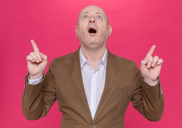 Kale man van middelbare leeftijd in pak opzoeken verbaasd en verrast wijzend met wijsvingers staande over roze muur