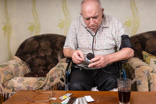 Kale man van middelbare leeftijd op zijn rolstoel, die zijn medicijnen controleert terwijl hij een bloeddrukapparaat vasthoudt in de woonkamer.